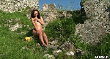 Голая девушка в горах сидит на валуне и дрочит