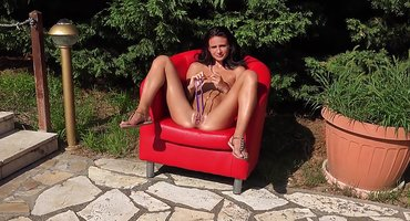 Девица во дворе на красном кресле дрочит игрушками вагину