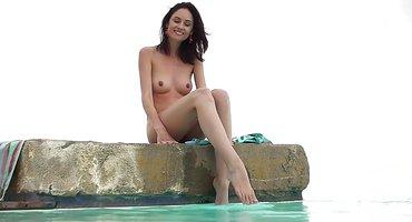 Брюнетка позирует без лифчика и трусиков в бассейне