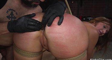 Хозяин разминает пальцами в перчатках очко связанной нижней