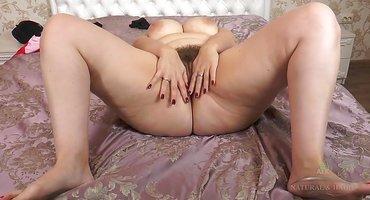 Толстушка на кровати сует пальцы в мохнатую щелку