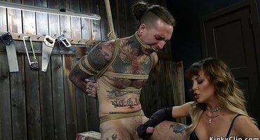 Госпожа связывает тугим шнуром яйца татуированного парня