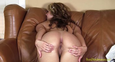 Милфа разминает пальцами на коричневом диване пилотку