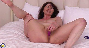 Полная женщина сует в растянутую вагину фиолетовый вибратор
