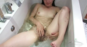 Молодка мастурбирует в ванне под водой дохматую щель